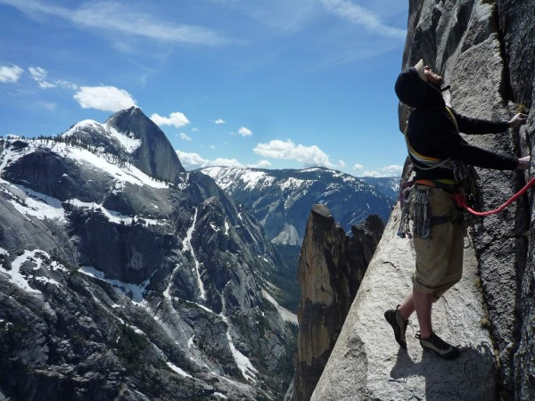 Tommy Caldwell about 4 pitches from the top. Snowy Half Dome in the ba...